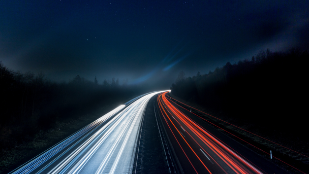A stream of lights coming from vehicles on the road at night taken by a camara with a slowed shutter speed setting