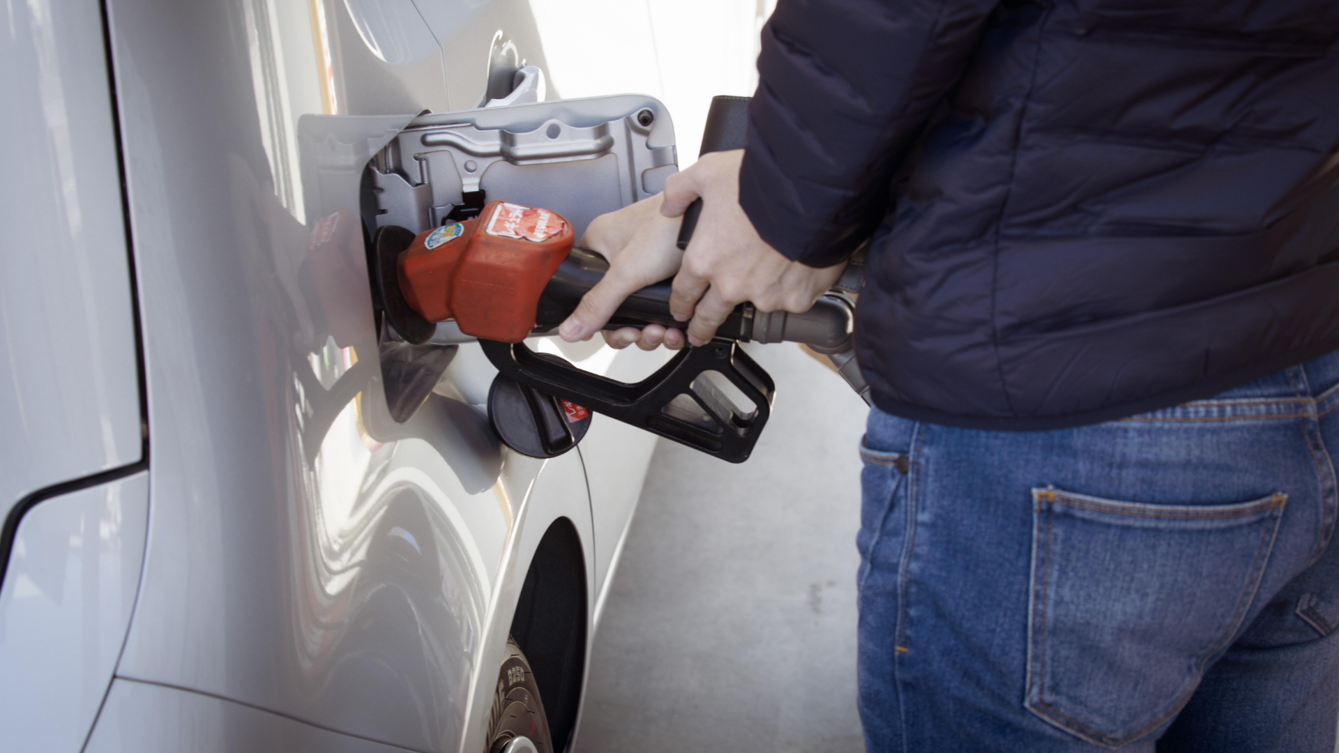 A person filling up their vehicle with gas