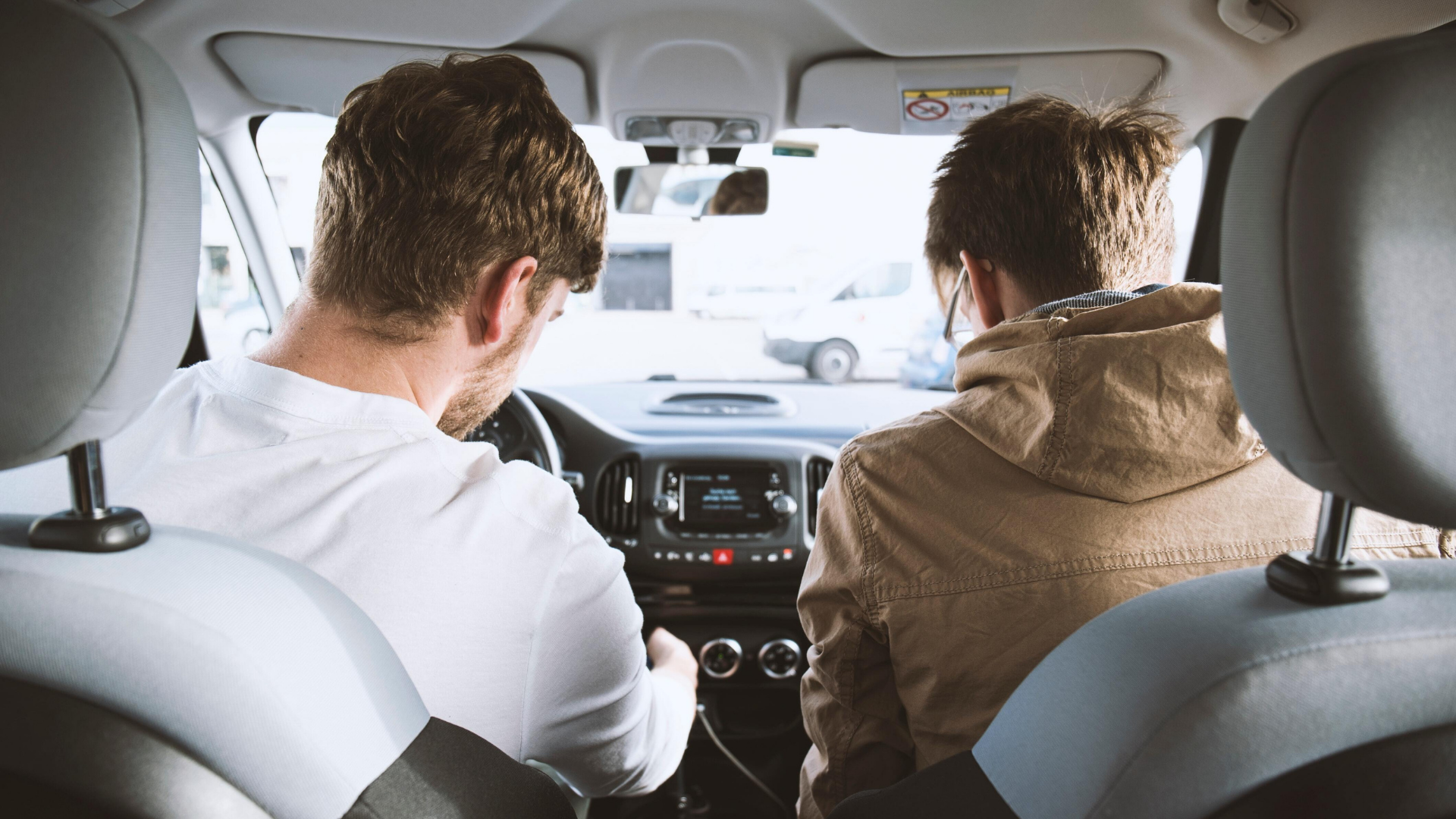 Two male passengers in a vehicle looking for a charging station on their phone