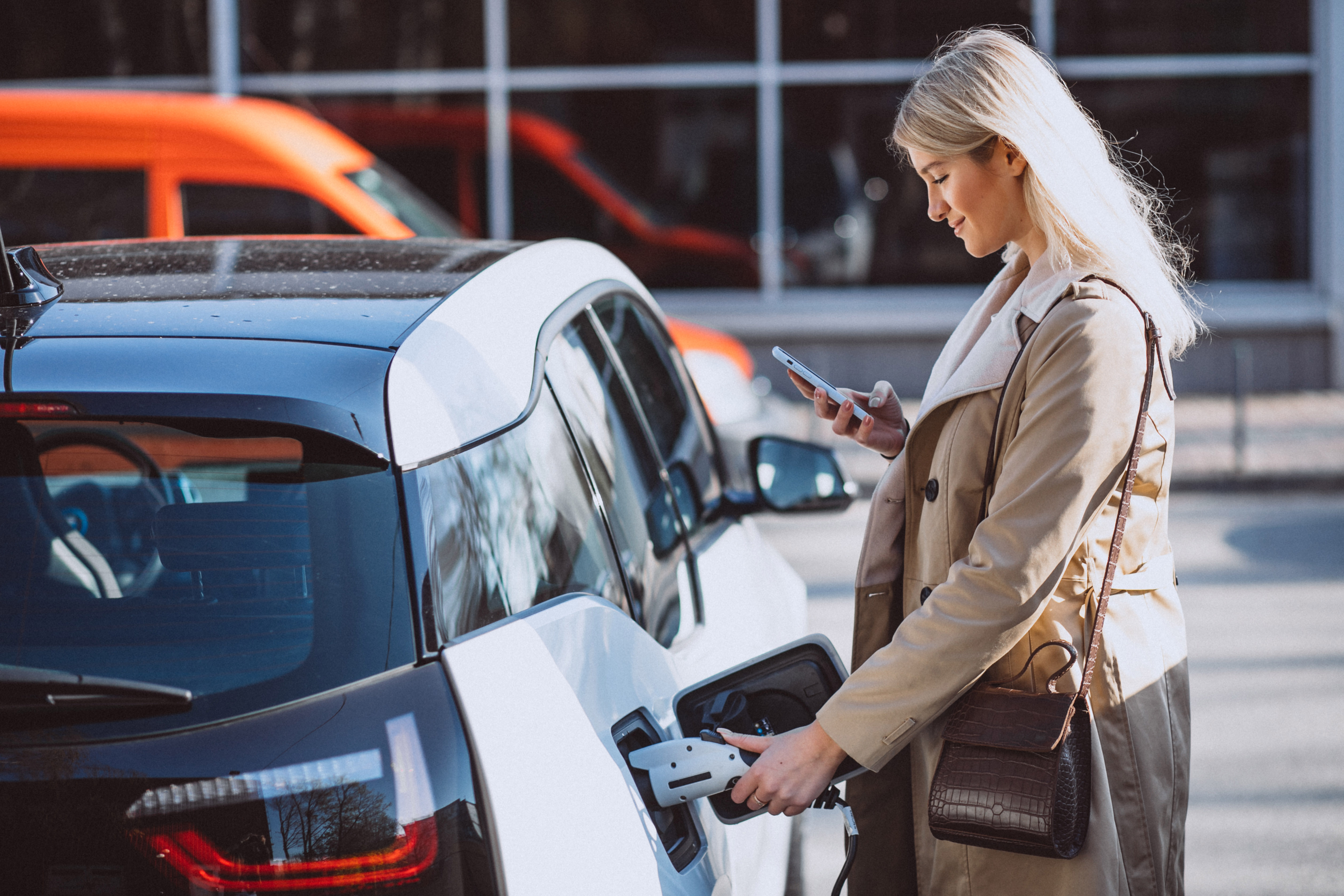 A young business woman that casually unplugs the charging cable from her car with her left hand, whilst checking important business updates on her smart phone with her right hand.