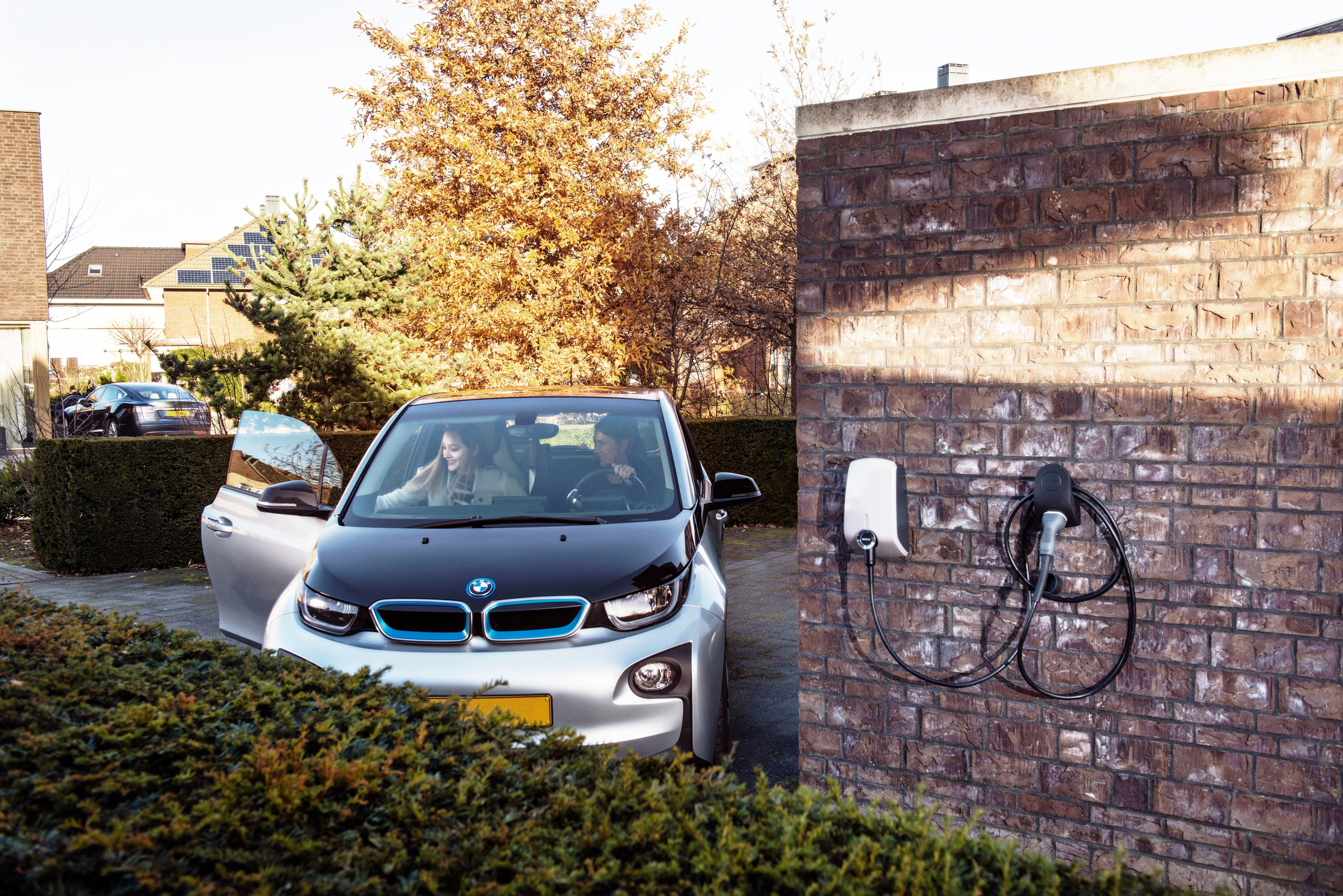 An electric BMW parking at a residential dwelling in the leafy suburbs next to a professionally installed EV charging station.