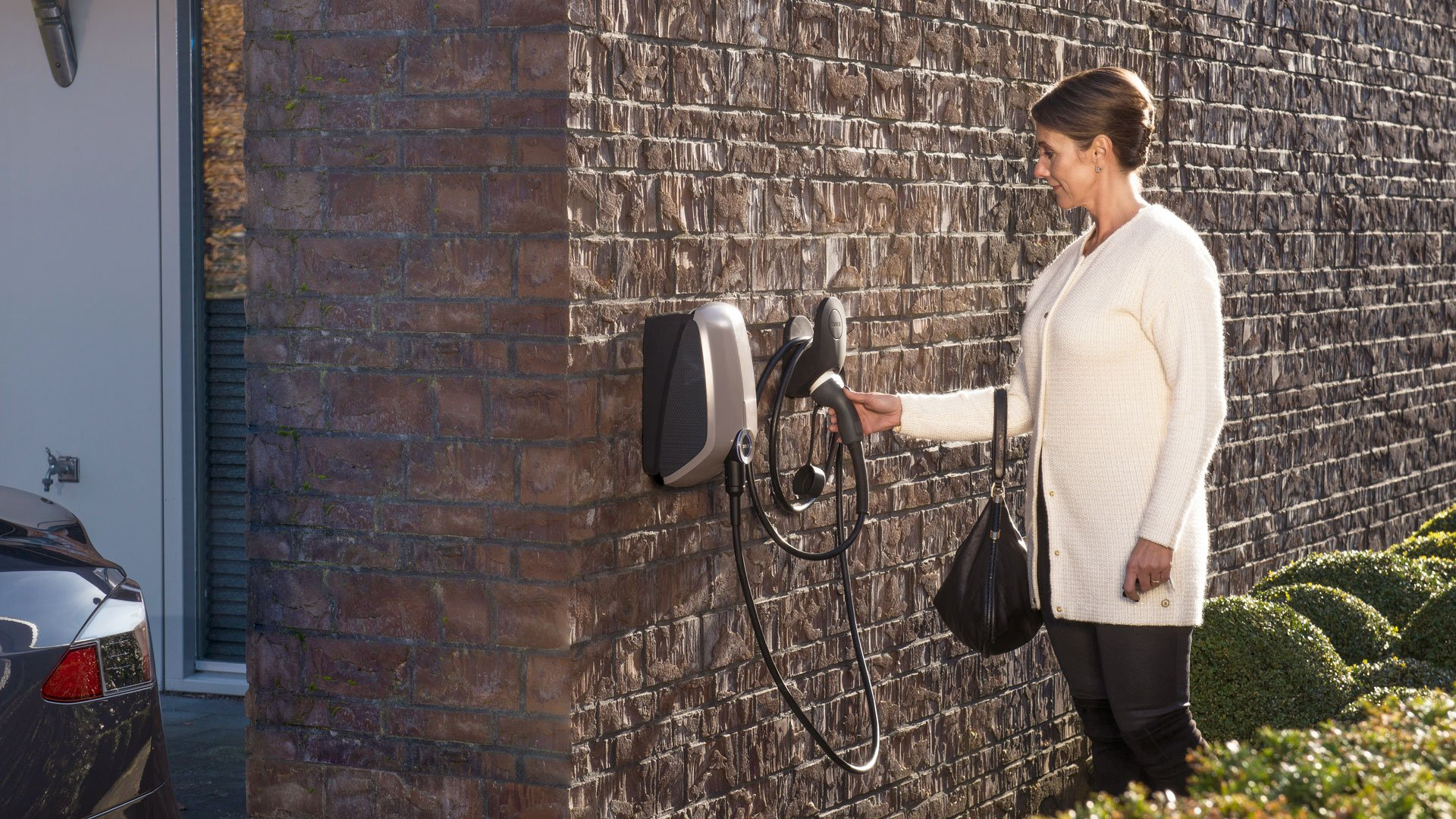 A woman grabbing the connecting cable of an EVBox Elvi Home charger mounted on the wall of her house.