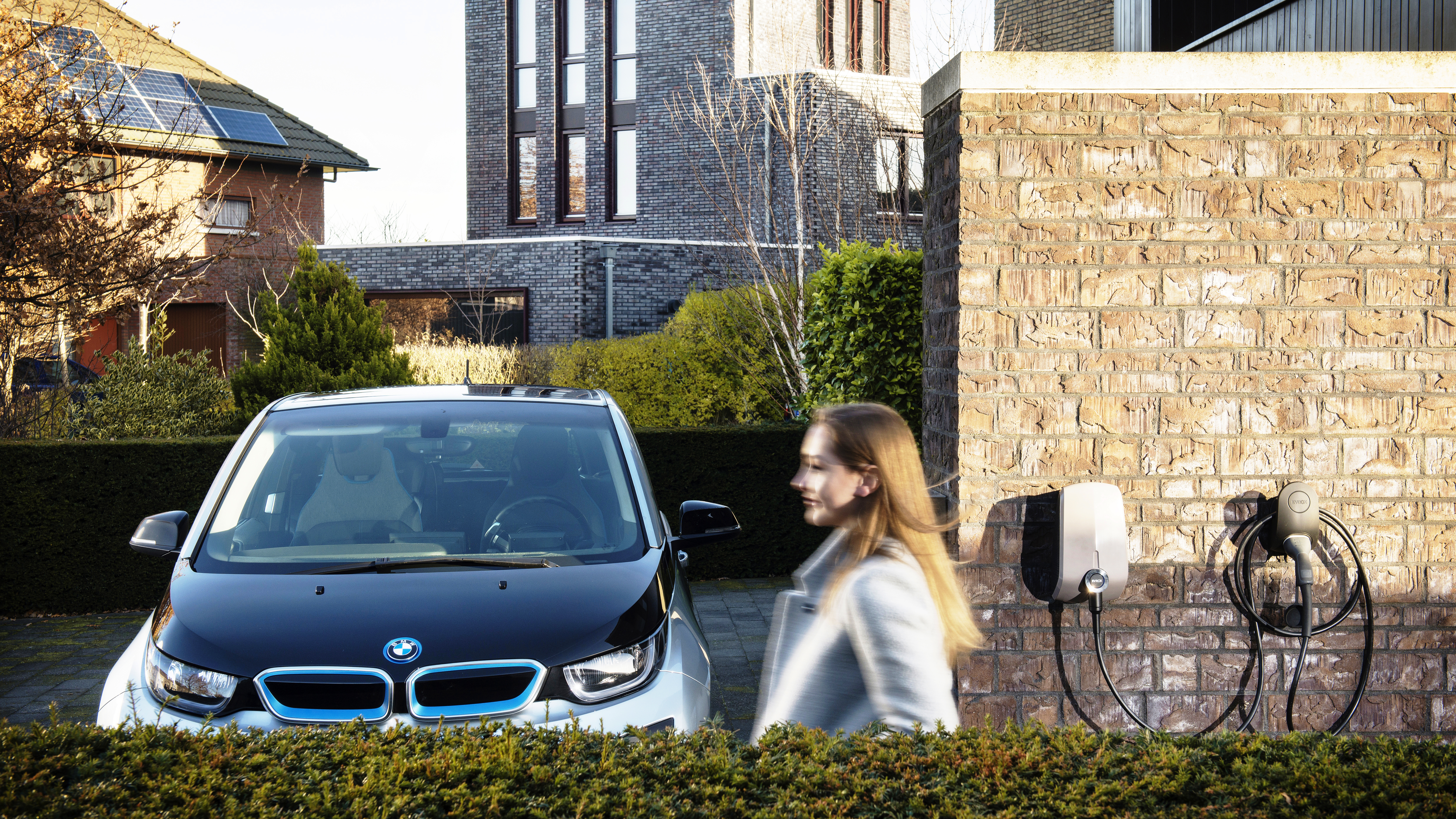 A woman passes a residential parking spot where an electric vehicle is parked next to a home charger on the wall.