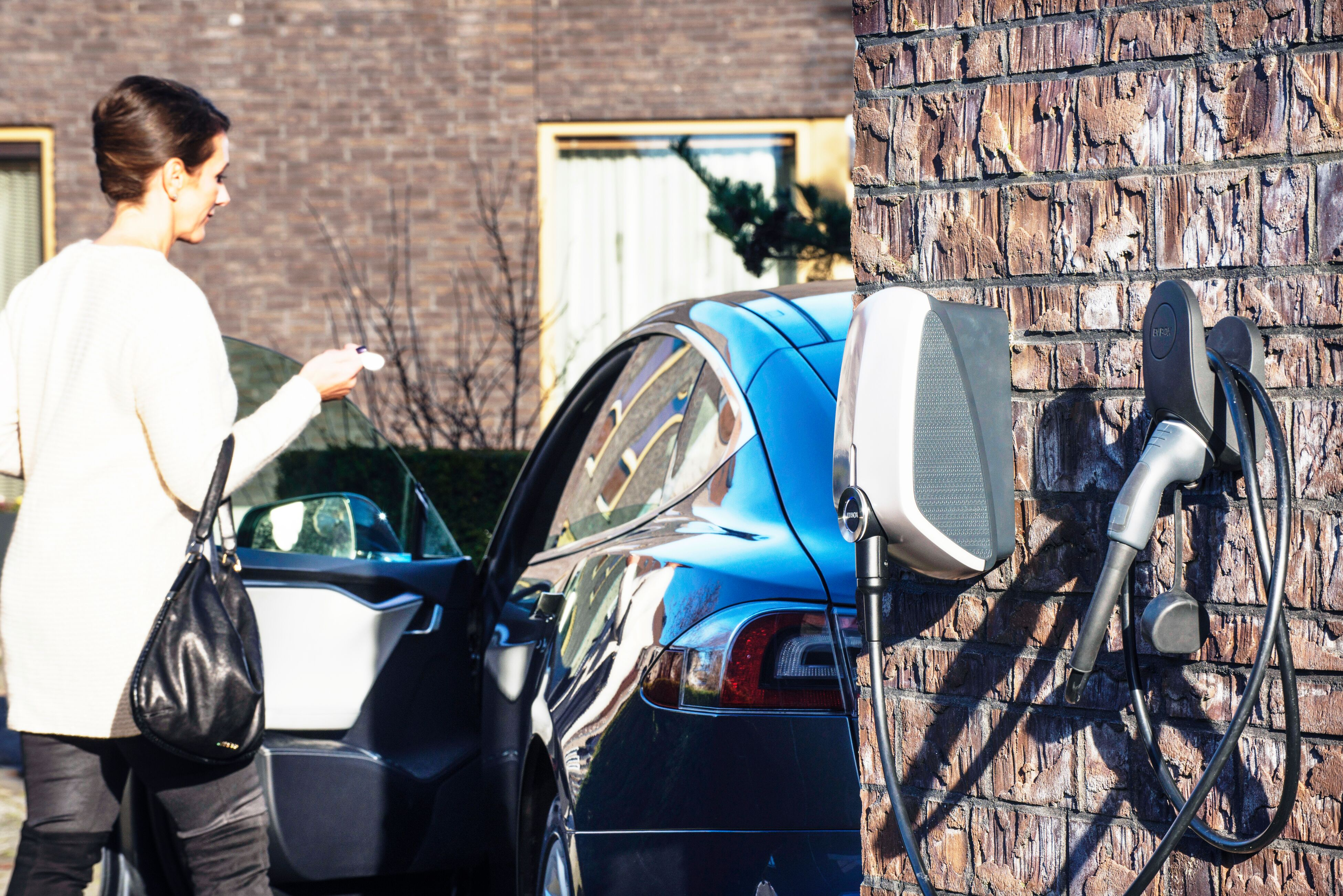 A woman entering her electric vehicle at her house, the exterior of the wall has an EVBox Elvi home charging station .