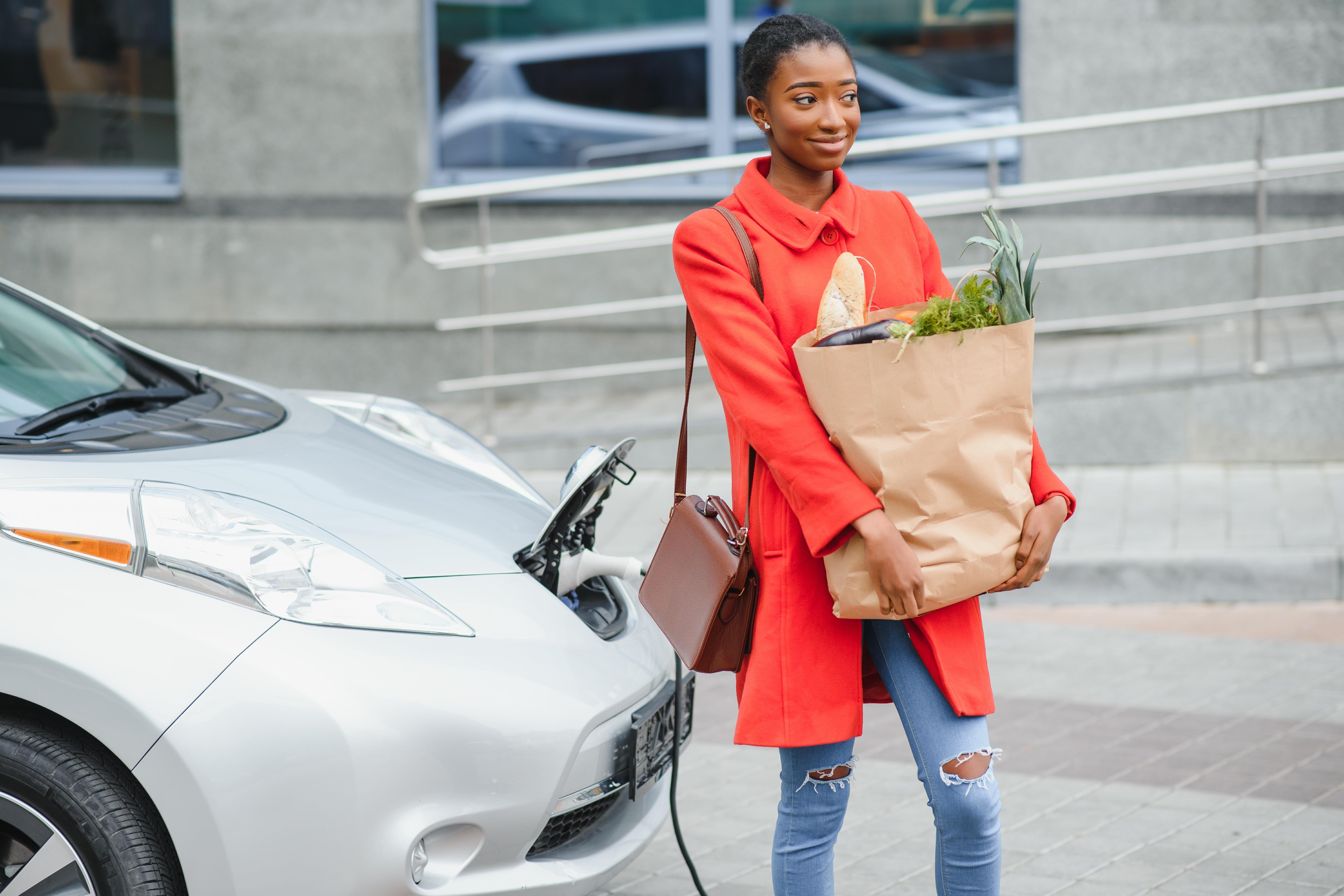 A professional-looking young woman charging her EV whilst picking up some groceries on her way home from work