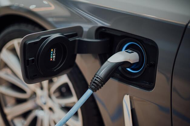 An electric vehicle charging via a charging cable that is equipped with modern lighting.