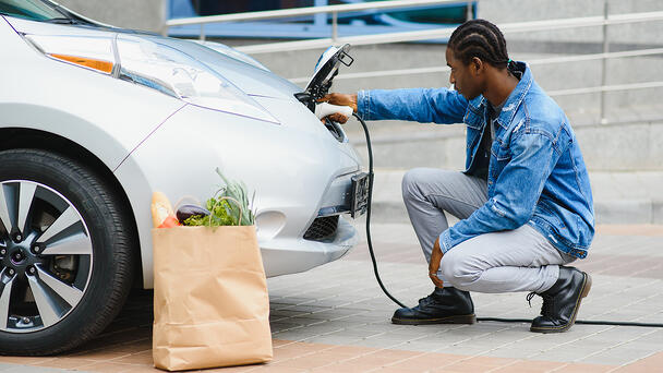 A handsome man in a denim jacket charging his EV with an AC charger after having done some organic shopping.