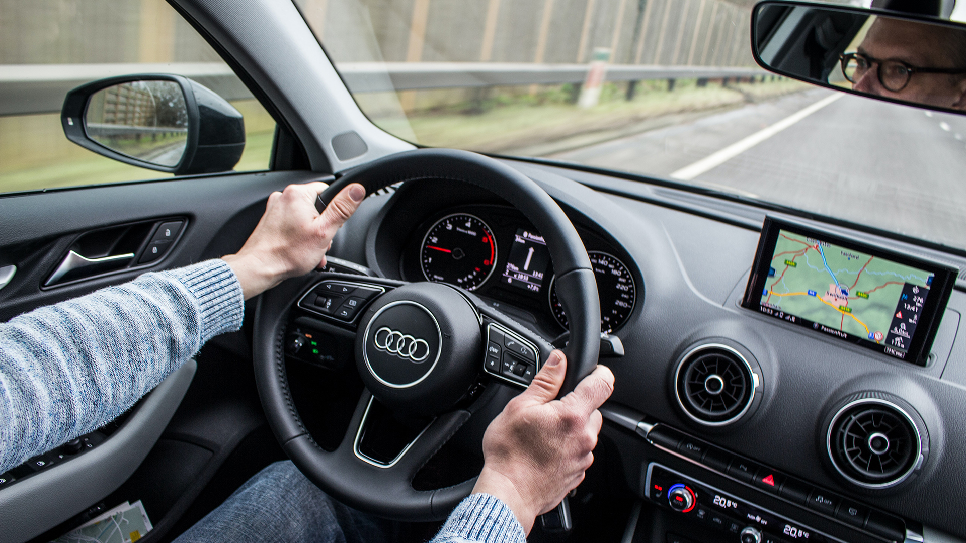 A middle aged man in a sweater driving an Audi in what looks like a moderately cloudy place.