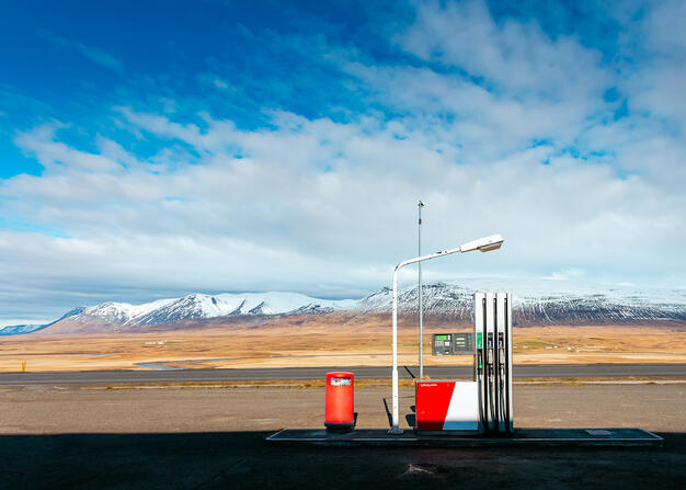An old-fashioned petrol station sits juxtaposed with the stark colours of the ice-capped mountains which lie beyond.