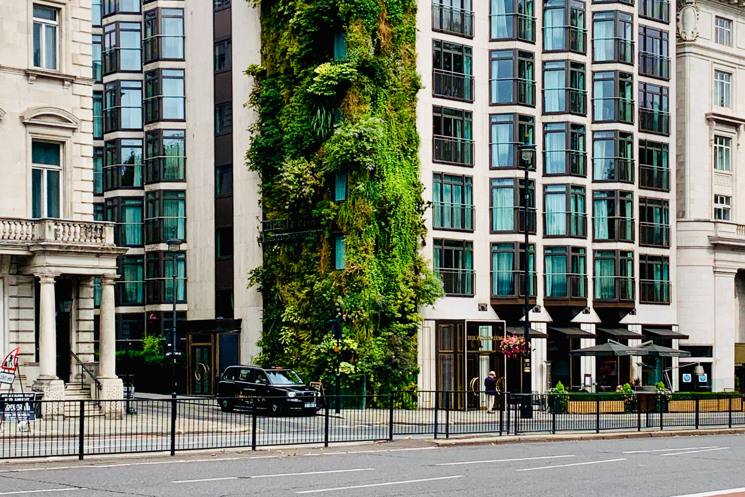 A green building in the middle of a city that showcases its plant-filled wall on the exterior-side of the building.