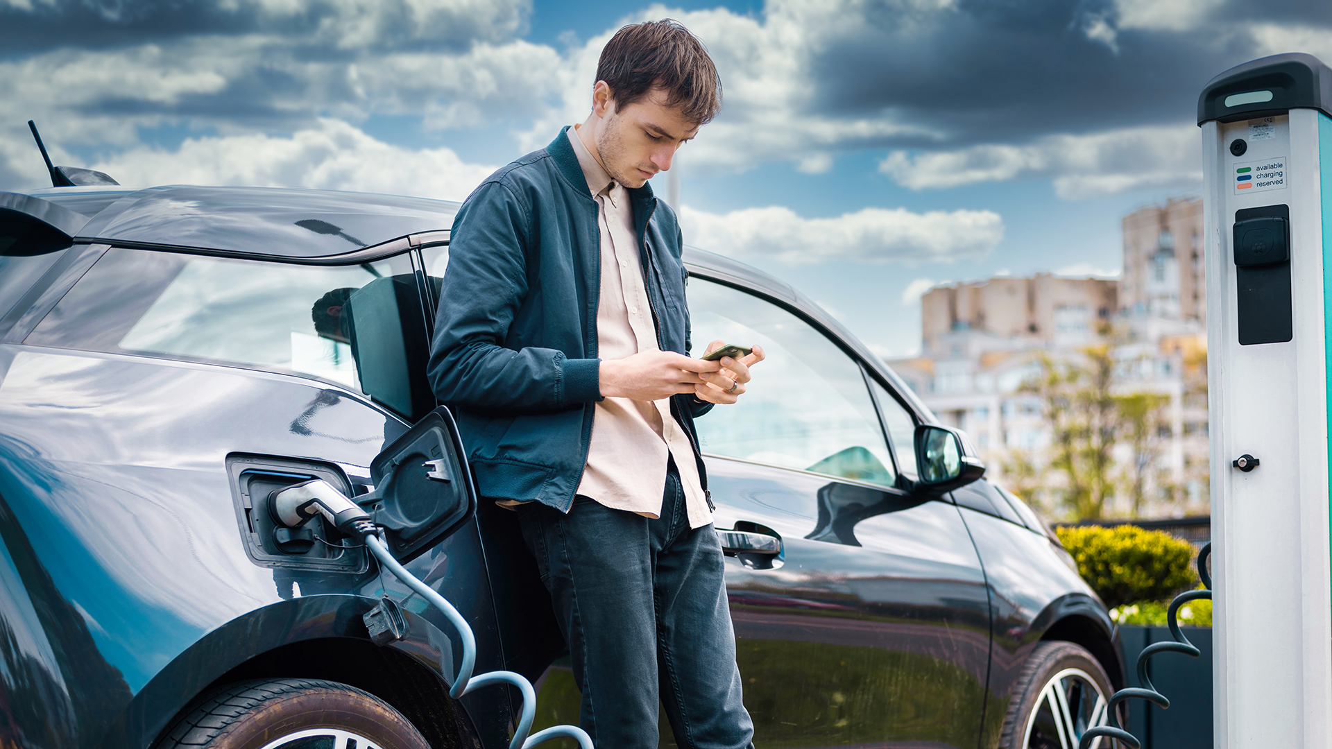 man-charging-his-electric-car-charge-station-using-smartphone