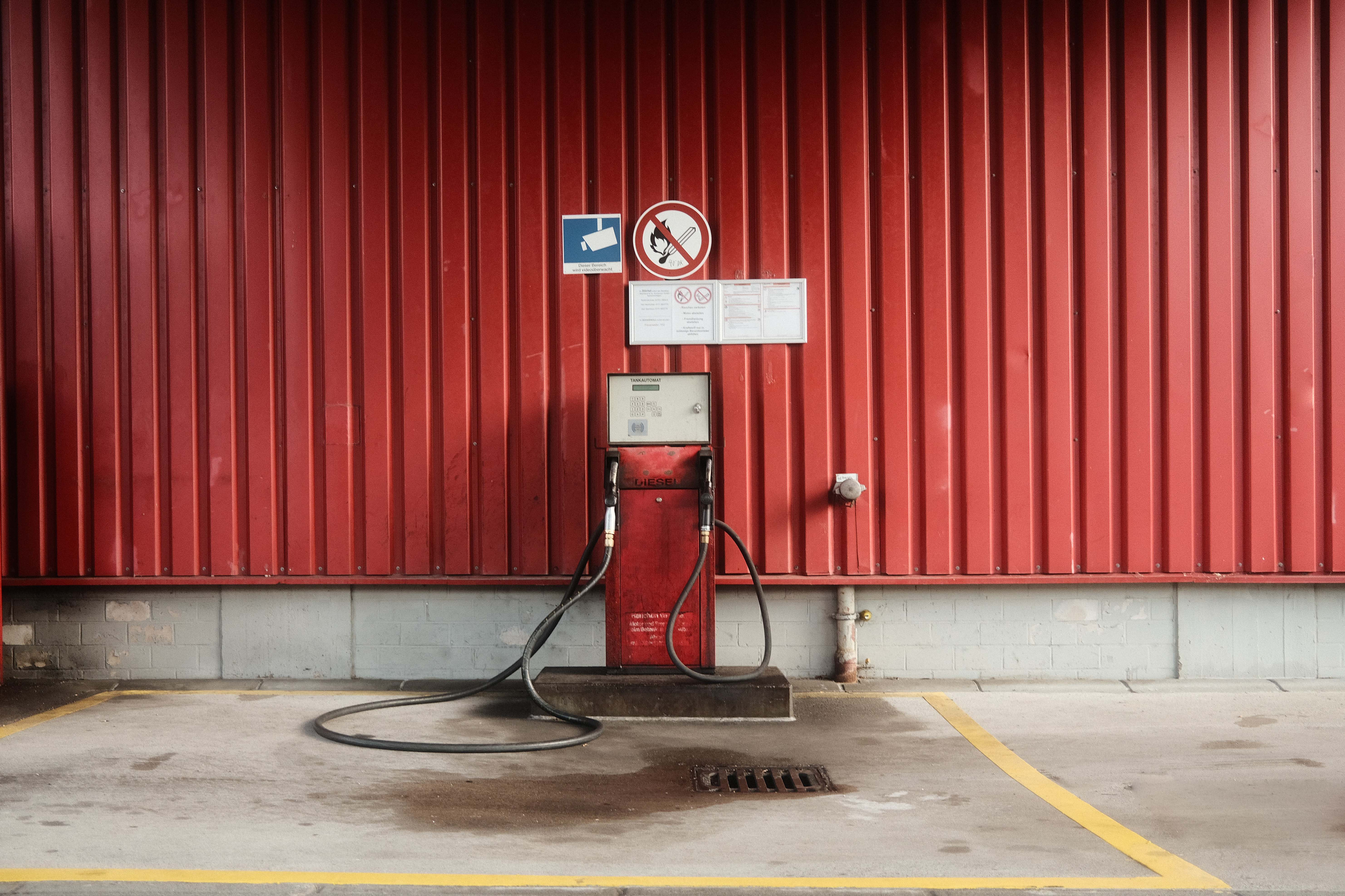 An old fashioned gas pump in front of a red wall in a dirty car park.
