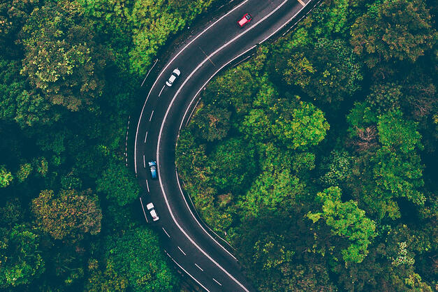 An arial shot of a winding three-lane highway in the forest.