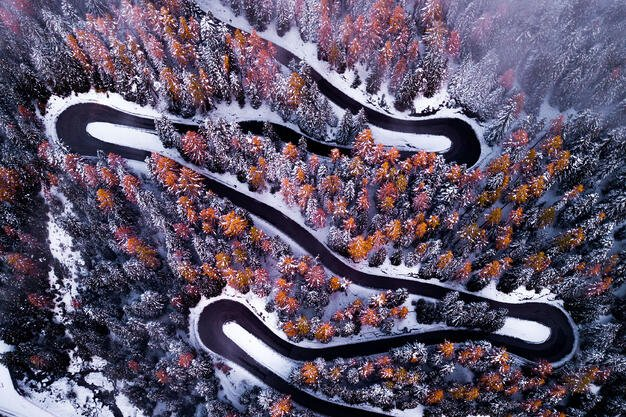 An arial shot of a snow-lined highway in the forest in winter.