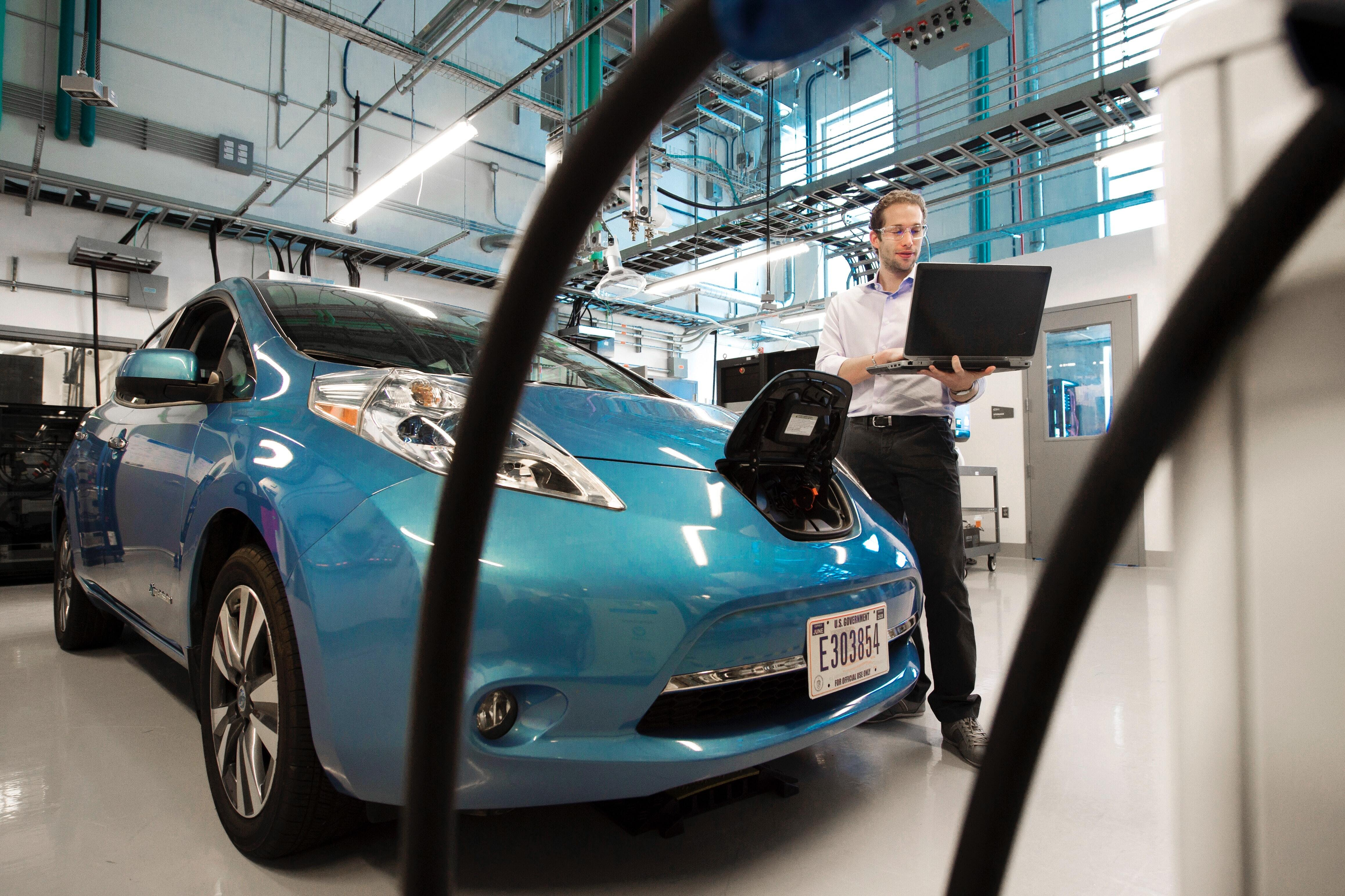 A man holding a laptop next to an EV, seemingly checking the status of the battery