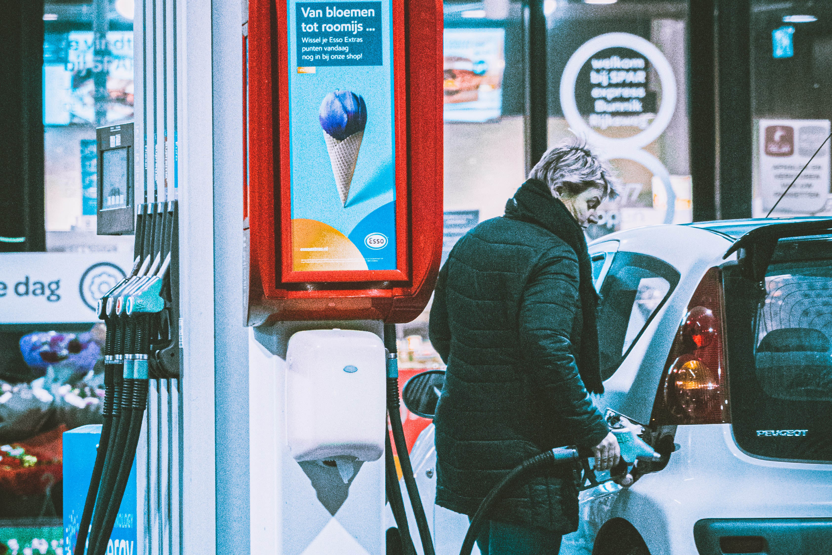 A women filling up her vehicle at a gas station besides an advertisement that offers everything from flowers to ice cream in Dutch.