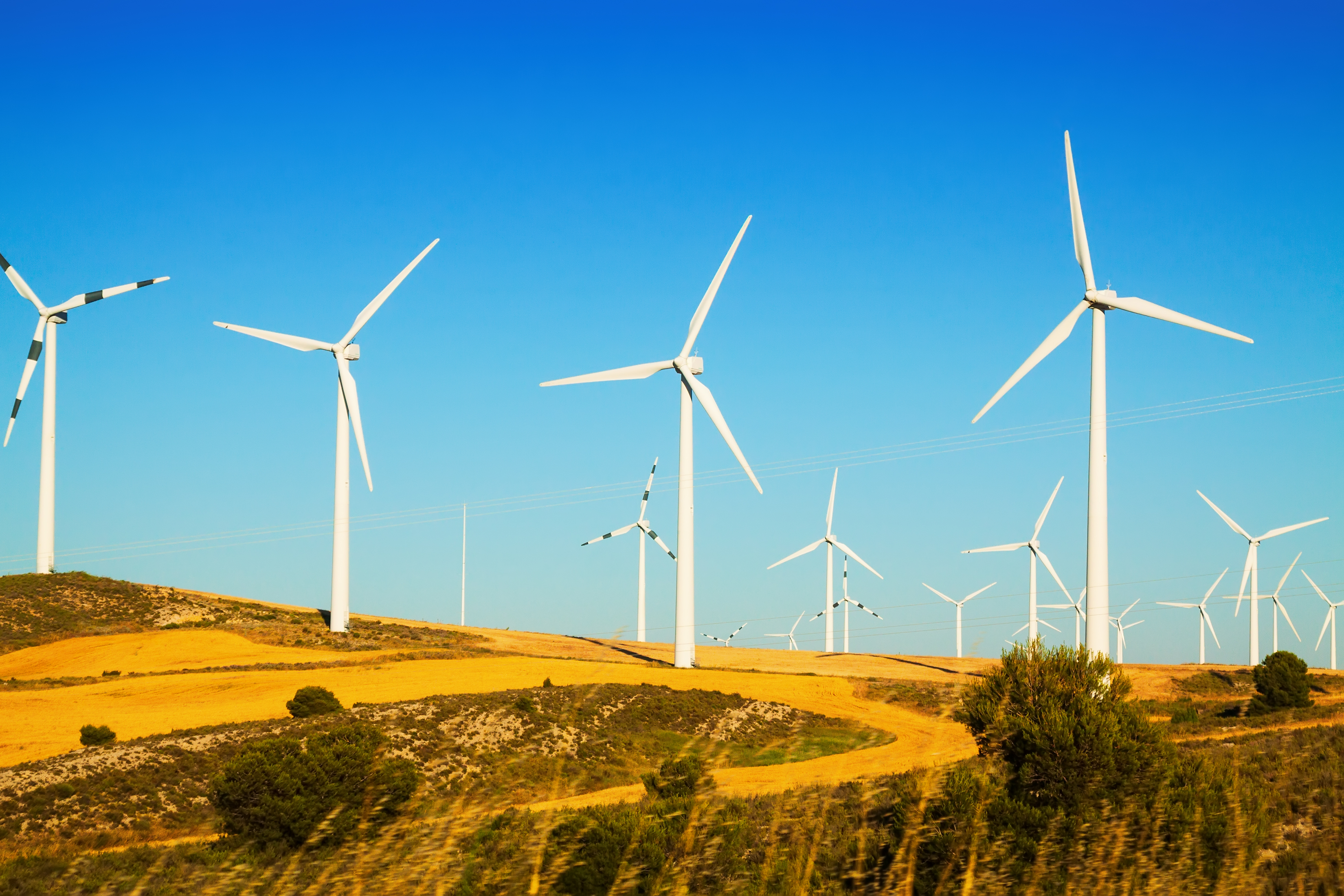 A wind farm with multiple windmills basking in the sunshine