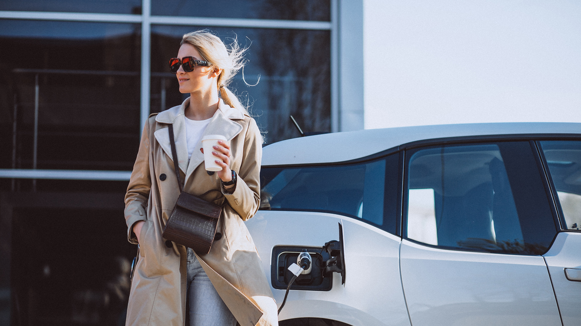 Lady gazing into the distance and looking content with a coffee whilst her EV is charging